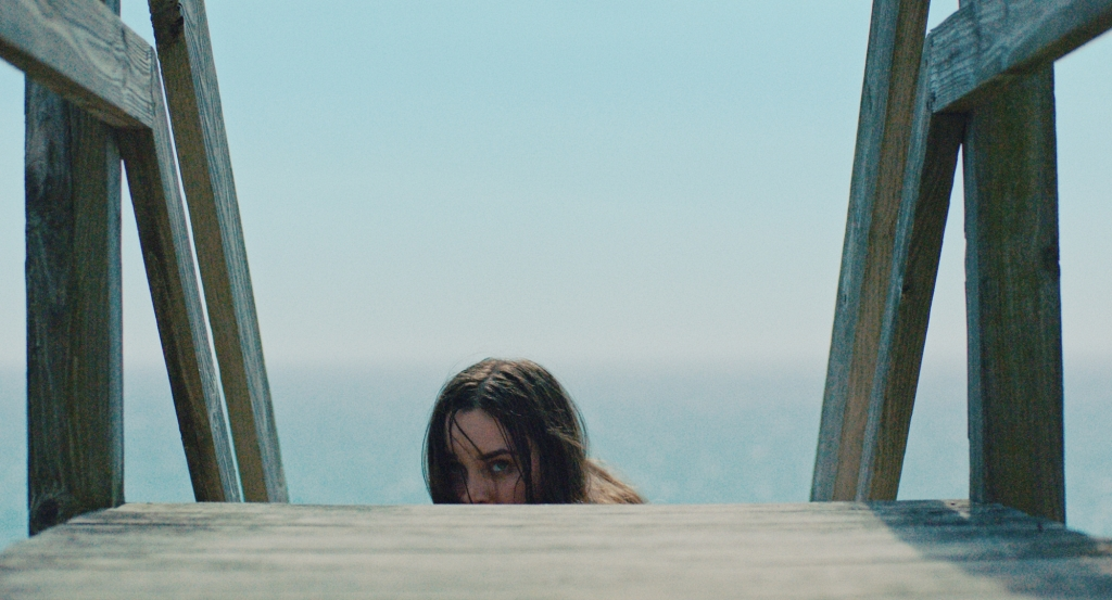A closeup shot of a young, brown haired girl climbing some wooden stairs that lead to the beach. Shot from a low angle you can only see half of her head emerging at the top of the stairs, she looks scared. The image is filled with blue as the sky and sea become indistinguishable.