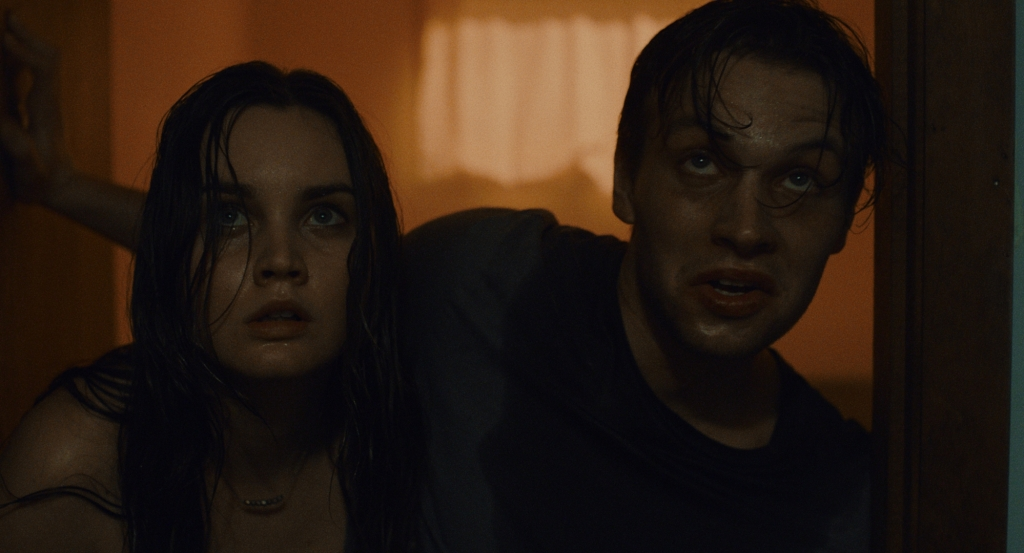 Emily (Liana Liberato) and Randall (Noah Le Gros), a 20-something couple are doused with sweat, supported each other and struggling through a corridor. They both look terrified. The image is a mid close-up of their heads and shoulders, you cannot see what they are looking at.