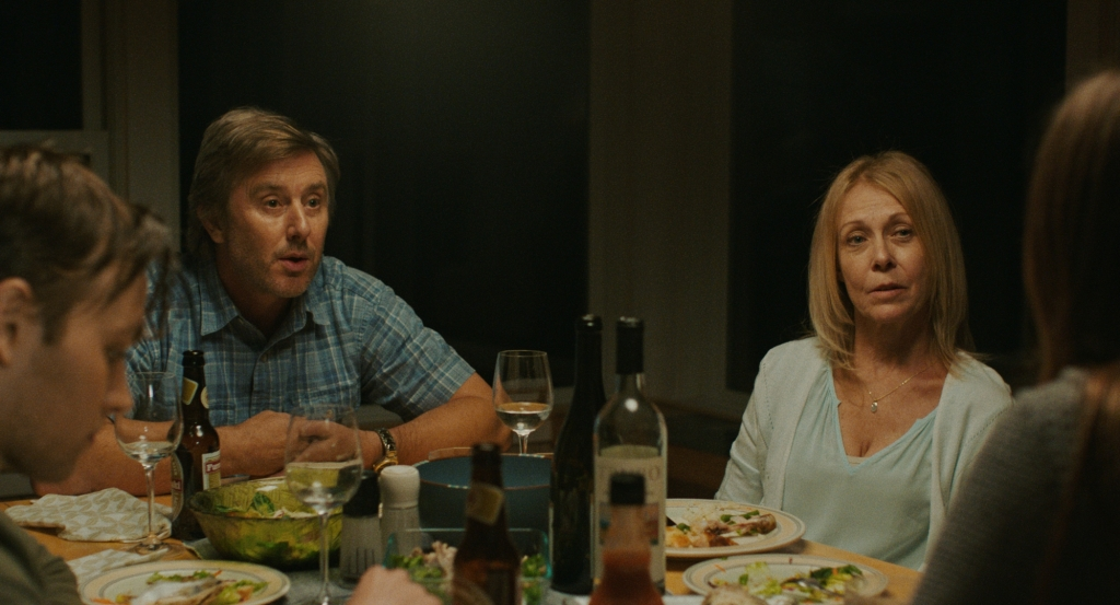 A white couple in their 40s/50s sit at a dinner table with two younger guests. They are mid conversation sat at a table filled with wine and food.