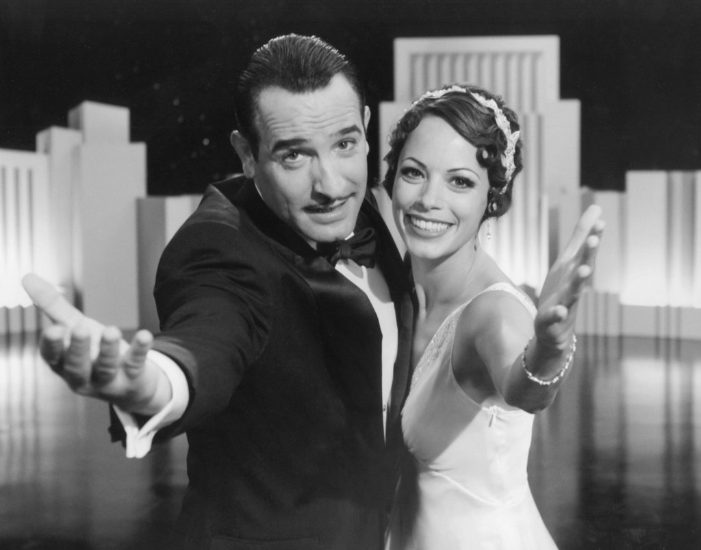 George Valentin (Jean Dujardin) and Peppy Miller (Bernice Bejo) look directly to camera, each with a beckoning arm. They are holding each other close, Peppy with a great smile on her face. Her hair is cropped in the 1920s finger waves style and a bejwelled headband adorns her hair. George has slicked back hair and a pencil thin moustache. He is wearing a tuxedo.