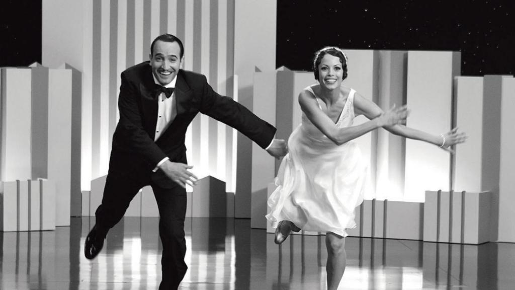 George Valentin (Jean Dujardin) and Peppy Miller (Bernice Bejo) are tap dancing in sync on a 1920s soundstage. The image is in black and white, this is a silent film era recreation. George wears a smart black tuxedo and Peppy has a 1920s cropped hairstyle and loose fitting white dress and matching headband.