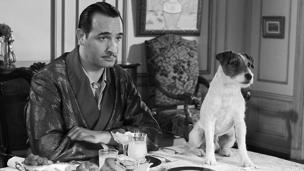 George Valentin (Jean Dujardin) sits with Uggie the Jack Russell dog. George is in a dining room 1920s setting wearing a silk satin smoking jacket with a floral print. He is a man around 40 years old with gelled back hair and a pencil thin moustache. Uggie sits at the table. His fur is primarily white but his face is presumably brown (the image is black and white).