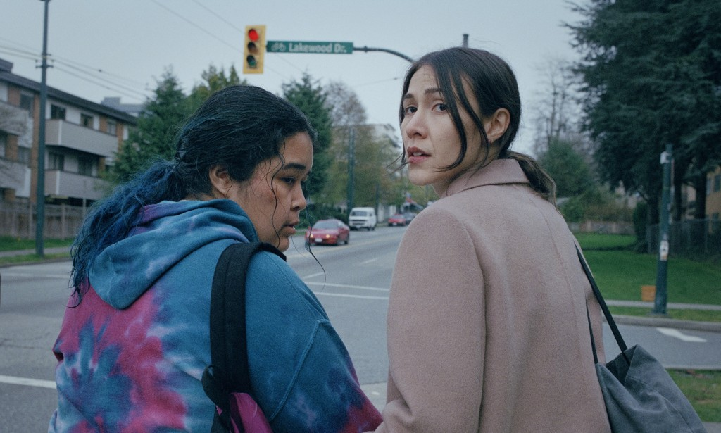 Violet Nelson and Elle-Máijá Tailfeathers in The Body Remembers When the World Broke Open. Both Indigenous women have their backs turned near a quiet road. Violet is wearing a purple and blue tie dye hoodie with a backpack over one shoulder. Her dark hair is soaking wet but you can see a hint of blue dip dye. She looks scared. Elle-Máijá is in office wear, all you can see is her tan wool coat and a grey tote bag over her shoulder. Her dark hair is pulled into a pony tail and she is looking back over her shoulder.