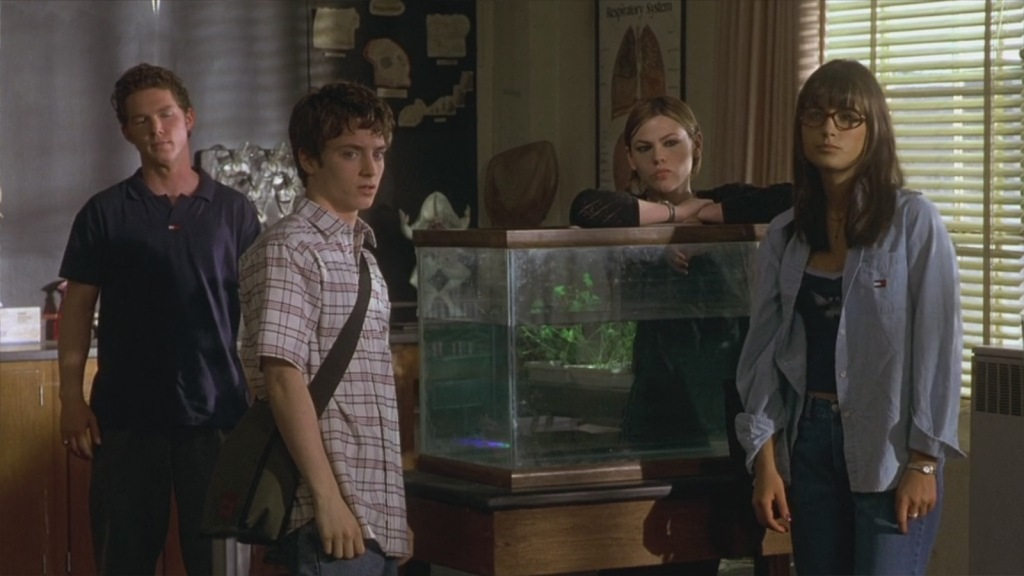 A still from the film 'The Faculty'. L-R: Stan (Shawn Hatosy), Casey (Elijah Wood), Stokely (Clea Duvall) and Delilah (Jordana Brewster) stand in a science classroom. Stan is a typical jock type, dark tshirt and curled hair. Casey wears a white checked shirt and over-the-shoulder backpack. Stokely stands behind a fish tank, leaning on it with her elbows. You can only see the top of ehr black jumper. Delilah looks like a popular girl, she wears an open tommy hilfiger shirt with a small vest top underneath and blue jeans. She has long dark hair and cglasses.