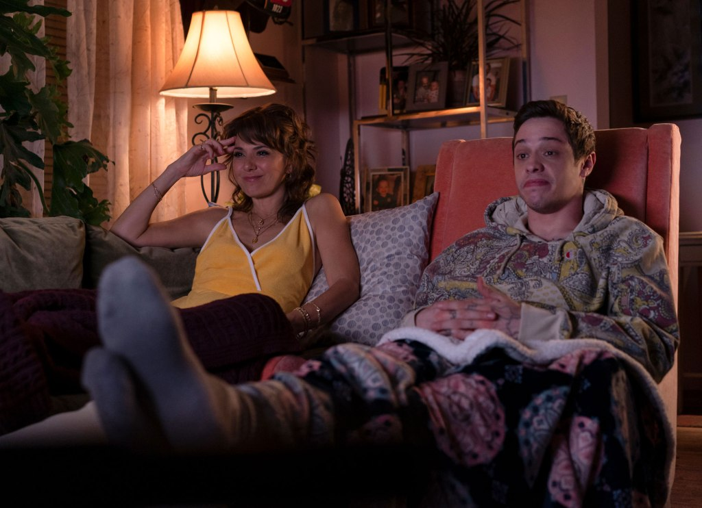 Margie (Marisa Tomei) and Scott (Pete Davidson) are sitting in their family living room. It is a cosy environment with a mish-mash of fabrics on their sofa and armchairs. A lamp glows behind the sofa that Margie is relaxing on and Scott sits at a pink armchair , behind him is a shelving unit filled with family photos.