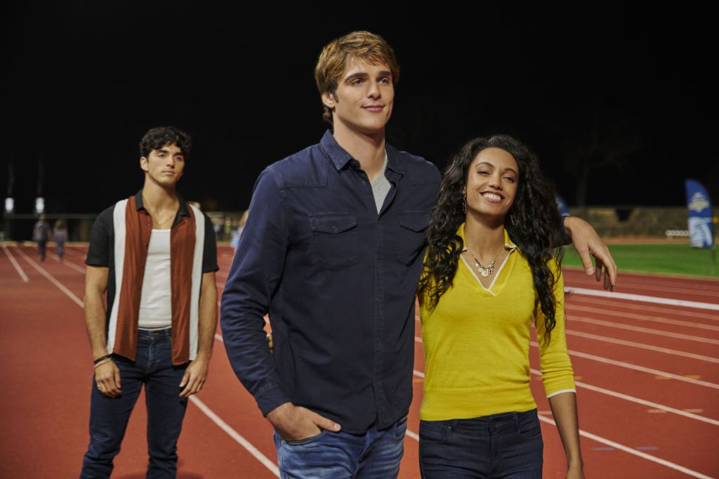 A still from 'The Kissing Booth 2'. Noah (Jacob Elordi) stands on a school running track with his arm around his girlfriend Rachel (Meganne Young). Noah looks incredibly smug, he is very tall and wearing a blue long sleeves shirt with a grey tshirt underneath. His short hair has a ginger tinge to it. Rachel is grinning ear to ear. She has dark skin and long black curly hair. She wears a yellow V-neck sweater and a gold coin necklace. Behind the couple, Marco (Taylor Zakhar Perez) stands in an open striped shirt with a white vest underneath. He looks angry.