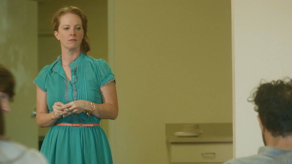 A still from short film 'The Potluck'. A woman in her 30s stands in an office, addressing a room of her colleagues. She has red hair and pale white skin. She wears a green tea dress with lace frills on the chest and a thin peach coloured waist belt. She has her hands clasped in front of her in frustration. Her face is visibly angry.