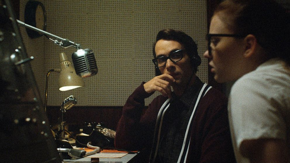 A young man and woman sit in a radio station. You can tell be their clothes and equipment it is the 1950s. The young man is wearing thick rimmed black glasses , headphones and a varsity cardigan. The young woman is partially out of frame wearing similar large thick rimmed glasses and a white shirt. The pair look confused.