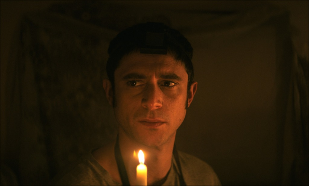A still from 'The Vigil'. Yakov (Dave Davis) is shrouded in darkness only lit by a candle he is holding. He is wearing the traditional Jewish Teffilin and looking scared to the right of the shot.
