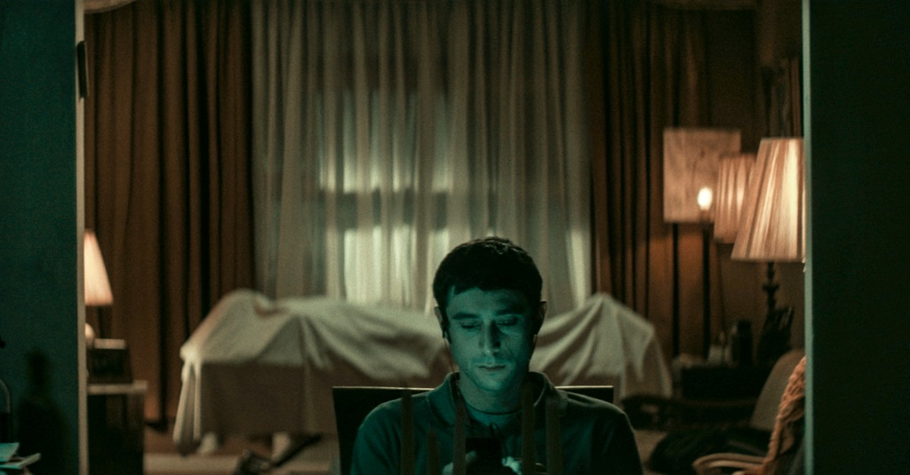 A still from 'The Vigil'. Yakov (Dave Davis) sits in a darkened, out-of-style living room. His face is lit up by his phone and his headphones are in. Yakov is plain looking, with short dark hair and a fleece jumper on. Behind him you can see a body that is covered by a white sheet. The curtains are closed.