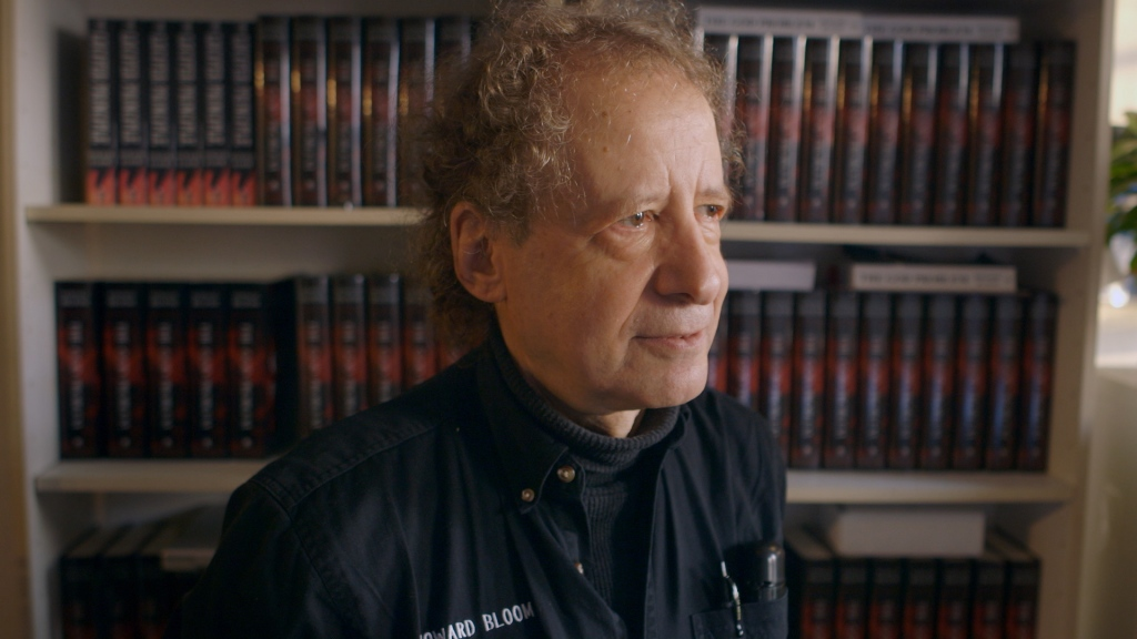 Howard Bloom stands in front of a filled bookcase. He is an older man, possibly in his 60s, with wild curly grey hair and a receding hairline. His eyes are brown and he is looking away from camera to his left. He wears a dark poloneck jumper and black shirt.