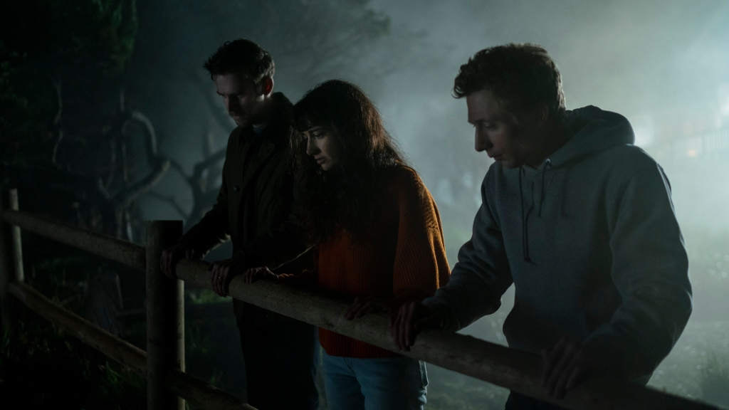 Charlie (Dan Stevens), Mina (Sheila Vand) and Josh (Jeremy Allen White) are standing on a cliffside guarded by a wooden fence. They are all looking down with concern. We cannot see the cliff drop or what they are looking at. Its a dark and misty night and all three of them are wearing jumpers and hoodies to keep warm.