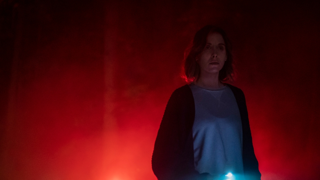 Michelle (Alison Brie) stands in a pale blue sweatshirt and baggy navy cardigan in a forest, alone. She is bathed in the red light of a car brake light, you can only just make out the outlines of trees amongst the mist.