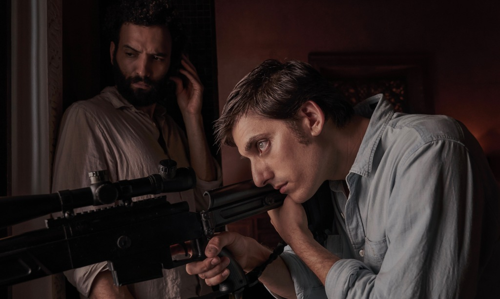 Marwan Kenzari (Joe) leaning against a wall. Luca Marinelli (Nicky) pointing a sniper rifle out of a window.