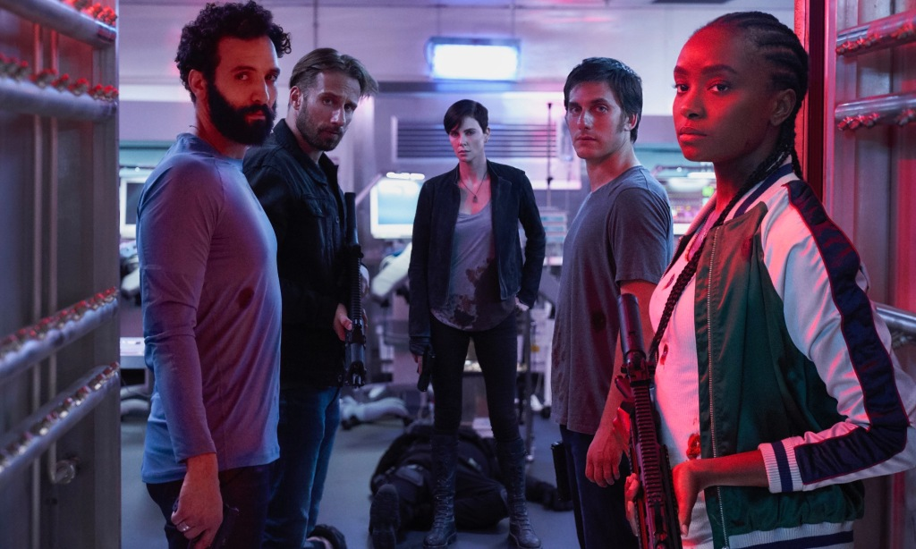 Marwan Kenzari (Joe), Matthias Schoenaerts (Booker), Charlize Theron (Andy), Luca Marinelli (Nicky), and KiKi Layne (Nile) standing with a red light shining over them.