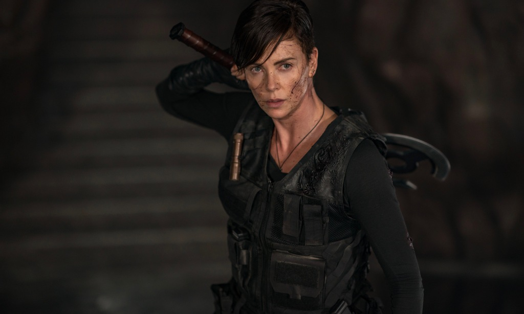Charlize Theron dressed in black tactical gear, wielding an ancient axe.