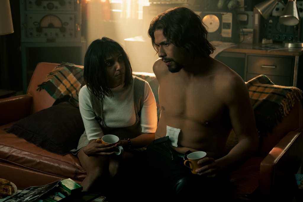(L to R) Rita Arya and David Castañeda seated on a brown leather couch with a yellow, gree, brown plaid blanket draped on the back of the couch. Arya leans forward towards Castañeda, who sits on the couch shirtless with a medium sized bandage on his stomach.
