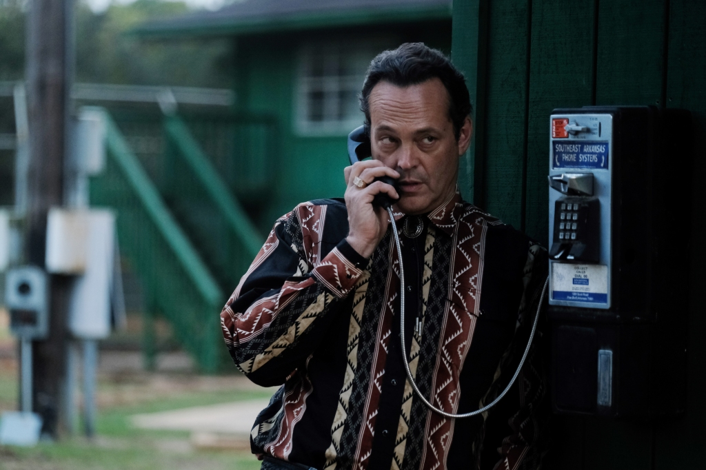 Frog (Vince Vaughan) is leaning against a pay phone holding the receiver. It looks like he is standing outside a motel or some sorts. His hair is dark and his eyes shifty, The hand holding the receiver has a big gold ring on his fourth finger. He wears a western shirt in patterned stripes in neutral tones and a black bolo tie.