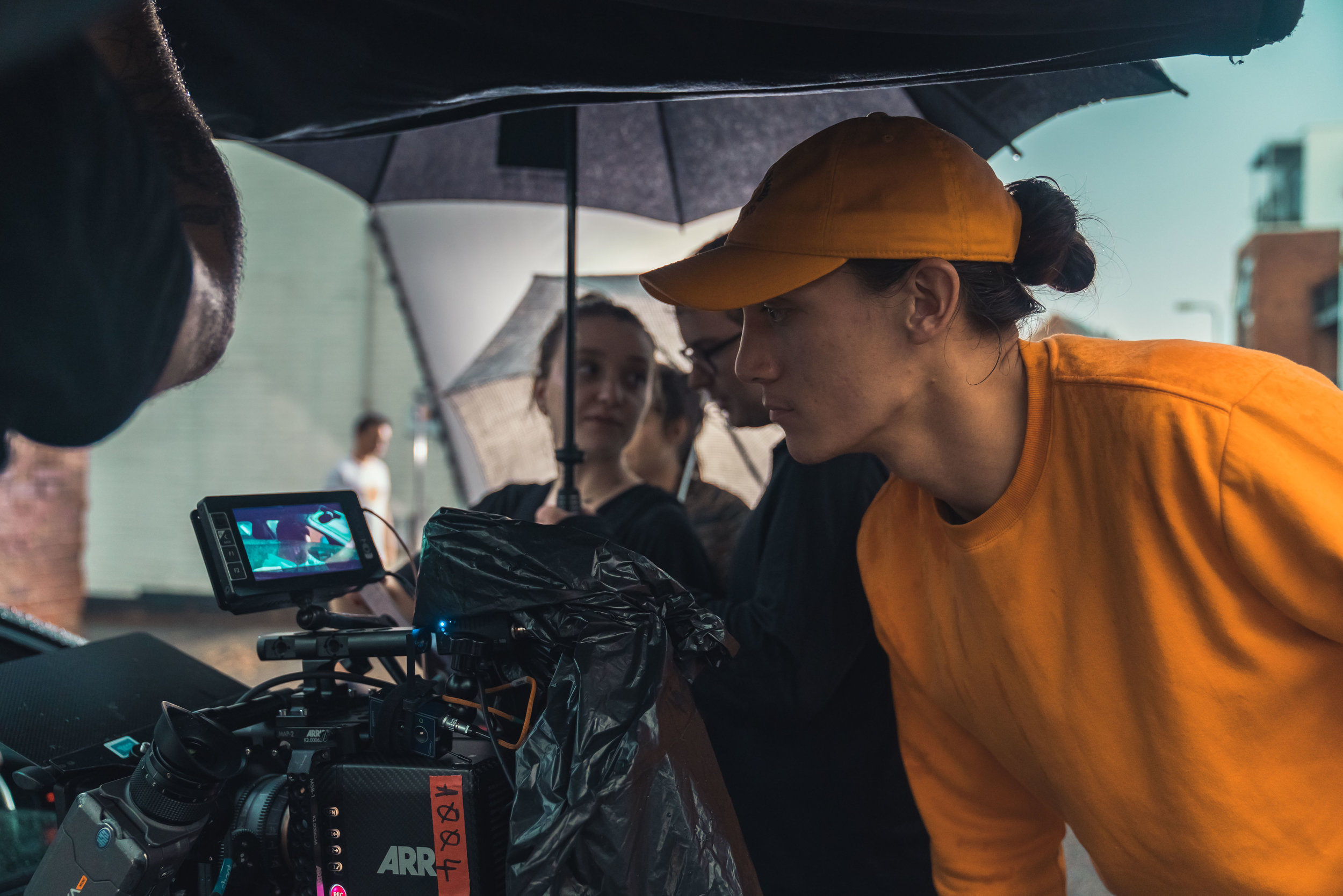 Behind the scenes of Stationary. Director Louis Chan, who has his brown hair in a bun and wears a matching orange sweatshirt and baseball cap, looks into the camera monitor, which is set up wrapped in plastic and under an umbrella because it is raining on set.