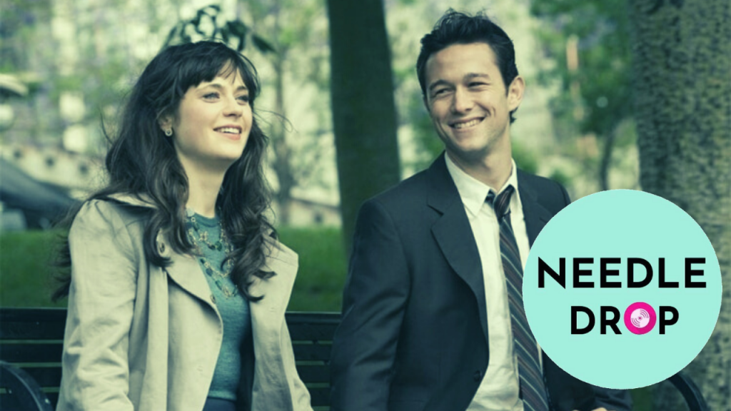 A still from '500 Days of Summer'. Summer (Zooey Deschanel) and Tom (Joseph Gordon-Levitt) sit on a park bench together. They are both smiling and Tom is looking towards Summer with affection. Summer has long dark hair and a fringe, wearing a trench coat with a grey jumper underneath. Tom is in a simple black office suit. The Needle Drop logo is edited into the bottom right of the image.