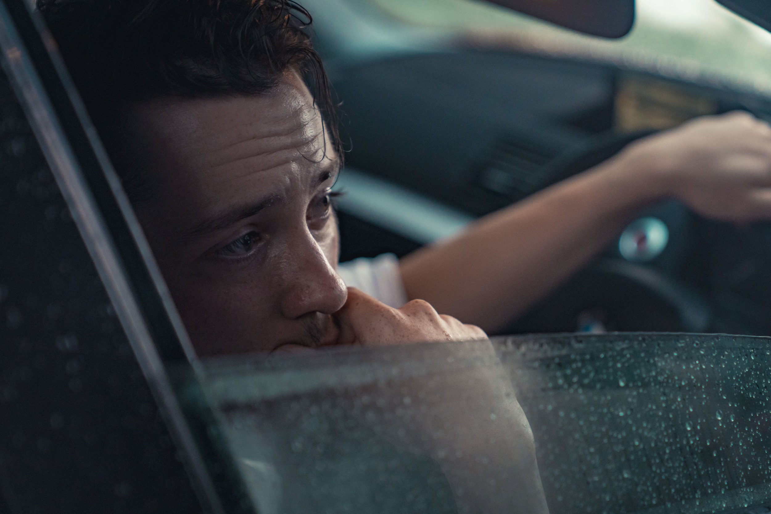Production still from Stationary. Jimmy, a white man in his late twenties, is sat in the driver's seat of a car, the window half rolled down and flecked with rain. His brown hair was slicked back but now falling into his face, his forehead is creased with worry. One hand is on the steering wheel and the other covers his mouth anxiously.