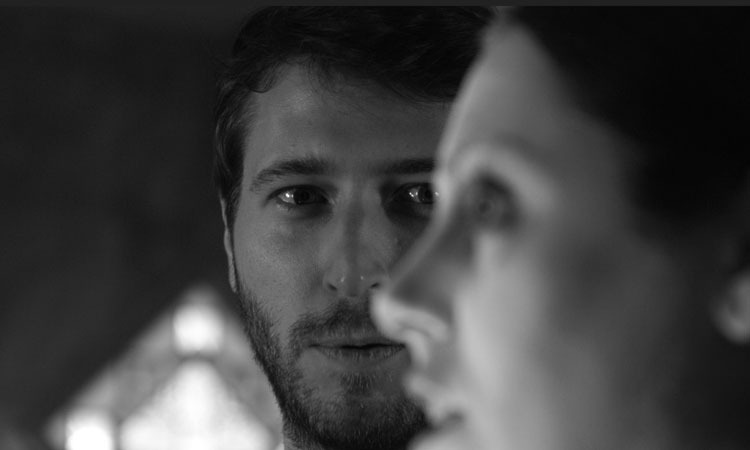 MacLeod Andrews and Natalie Walker in A Ghost Waits (2020). A black-and-white close-up of two faces. In focus in the background is Jack, his mouth tightened and his eyes trained on the ghost, who stands in front of him, out of focus in the foreground, staring off to the left of the frame.