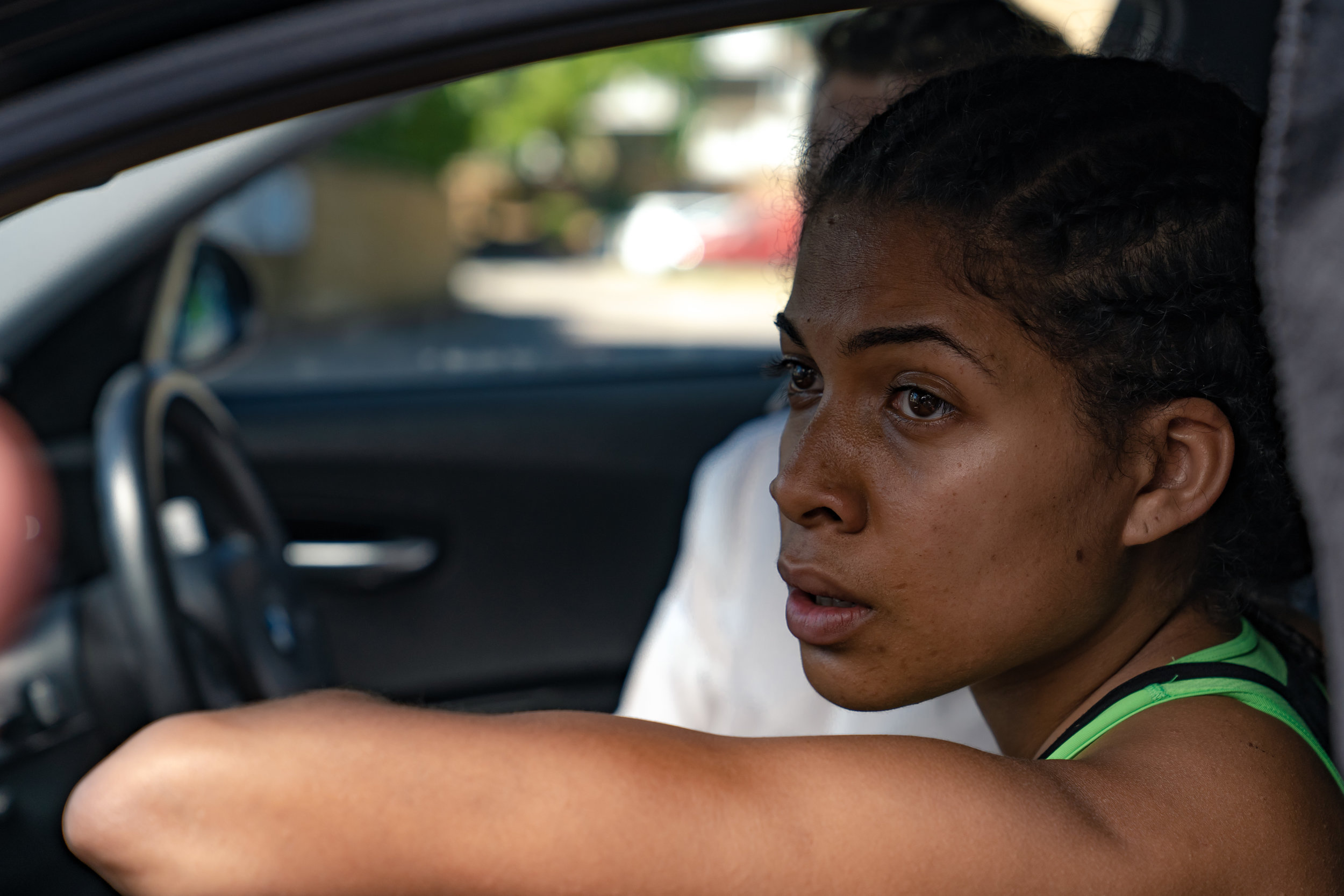 Production still from Stationary. A close-up on Che, a Black woman who looks to be in her late twenties, sits in the passenger seat of a car, her elbow propped up on the open window of the car door. She wears a lime green sports bra with a black vest over it, and is gazing intently into the distance, her mouth slightly open.