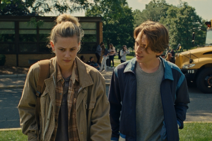 Lili Reinhart and Austin Abrams walking away from school. The building, students, and a school bus are visible behind them. Lili is wearing a baggy brown jacket, a brown plaid shirt, and a grey tshirt. Austin is wearing a blue sports/track jacket, with a grey tshirt. Austin's head slightly faces Lili as he talks.