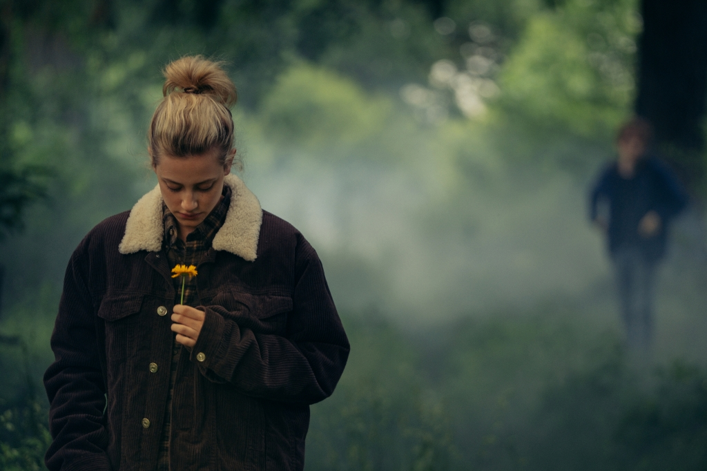 A still from 'Chemical Heart'. Lili Reinhart in the foreground walking in a forest. The forest behind her is blurry as is Austin who stands in the right side of the image.