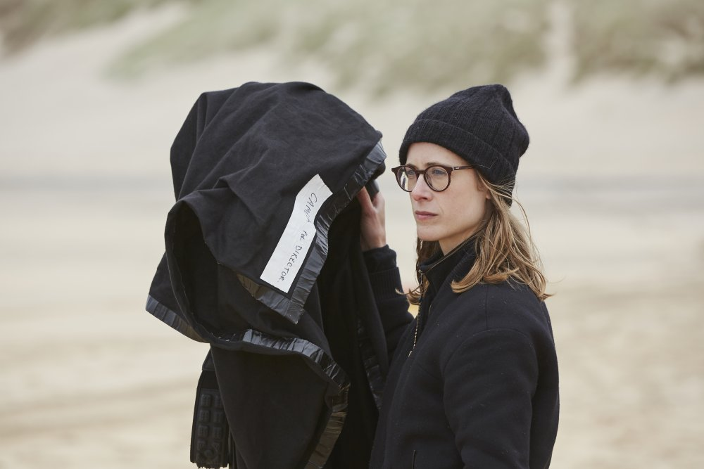 Behind the scenes of Make Up (2019). Director Claire Oakley is standing on a beach, the sand and grassy hill behind her is out of focus. Claire is white, has light brown hair to her collar and wears round brown glasses. She has on a black coat and a black beanie hat, it looks breezy. She is holding a large black sheet which is covering a camera.