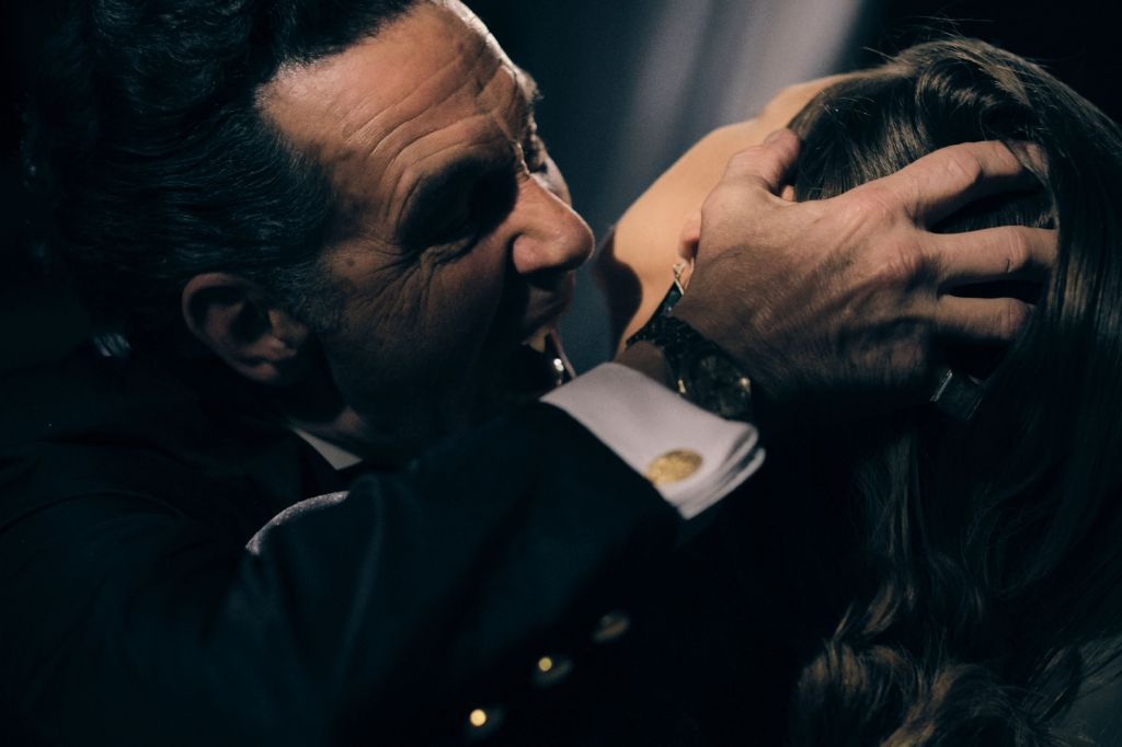 A still from 'Climate of the Hunter'. Wesley (Ben Hall), a vampire, is shown in close up here biting a woman's neck. The image is dark and sensual, his hand gripping the woman's head to turn her neck to him. He is a gentleman in his 40s/50s with slightly greying hair and deep brow wrinkles.