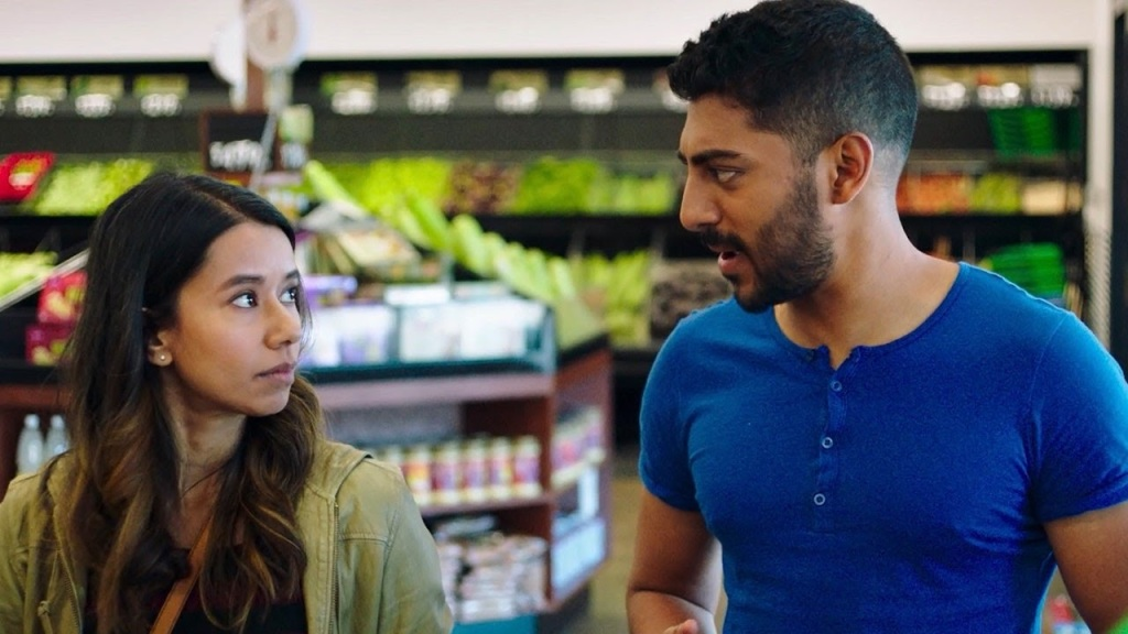 A still from 'Definition Please'. Monica (Sujata Day) and Sonny (Ritesh Rajan) are shown in a close-up in a grocery store. They are brother and sister of Indian descent. Monica has long dark hair and is wearing a khaji jacket, she is looking towards Sonny who is speaking, He is wearing a blue shirt with buttons down the front.
