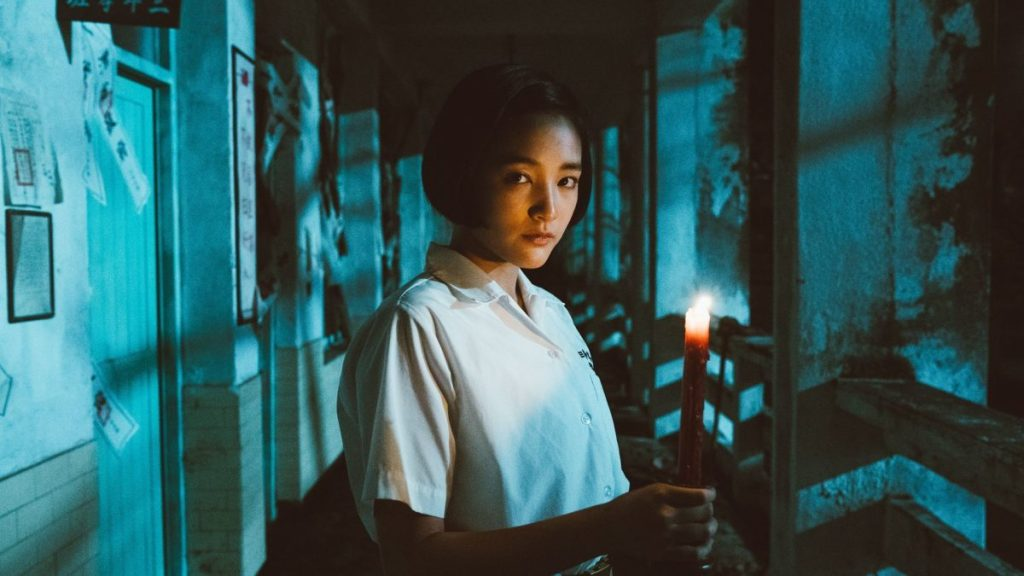 Gingle Wang stands in a dark and decrepit school hallway wearing a white school uniform shirt and holding a burning red candle stick.