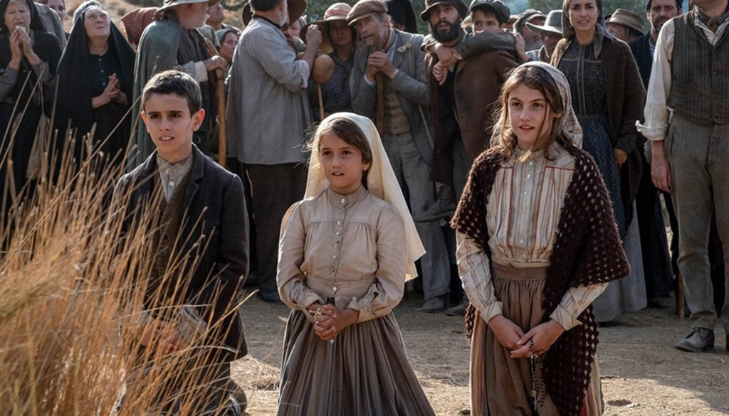 A still from 'Fatima'. Set in 1917, three children kneel in front of something or someone out of shot. There is a huge crowd of people behind them. They are all working class/lower class people in workwear and muted tones.