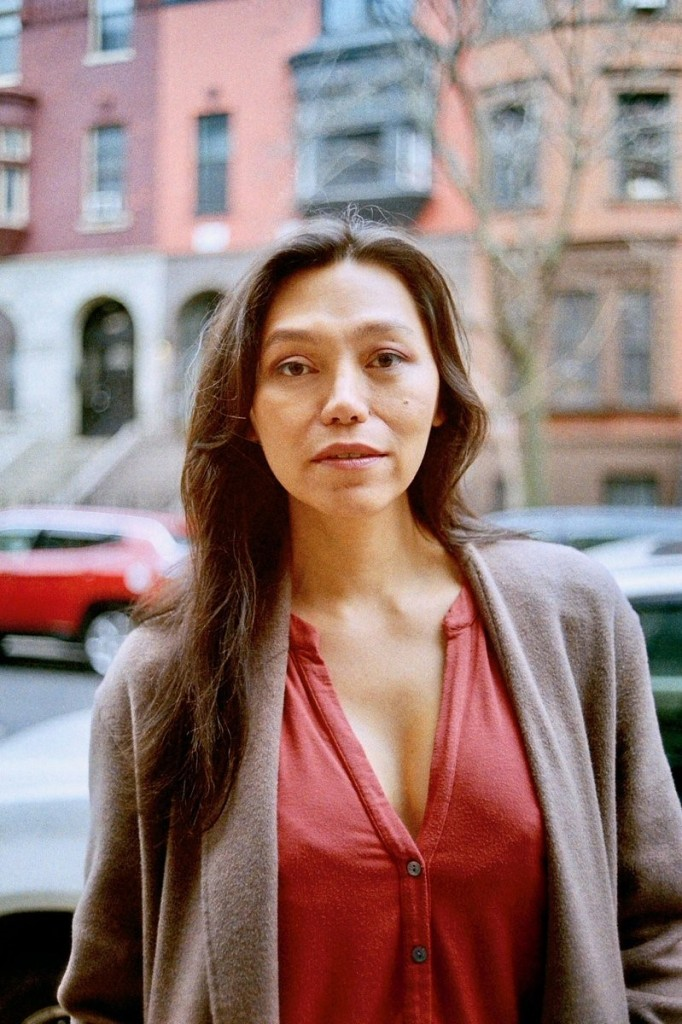 Headshot of director Isabel Sandoval. She is a Filipina trans woman, 38 years old with long dark hair and dark eyes. She gazes directly at the camera, her mouth slightly open. She is photographed on a busy New York street, wearing a V-neck red shirt and wool grey blazer.