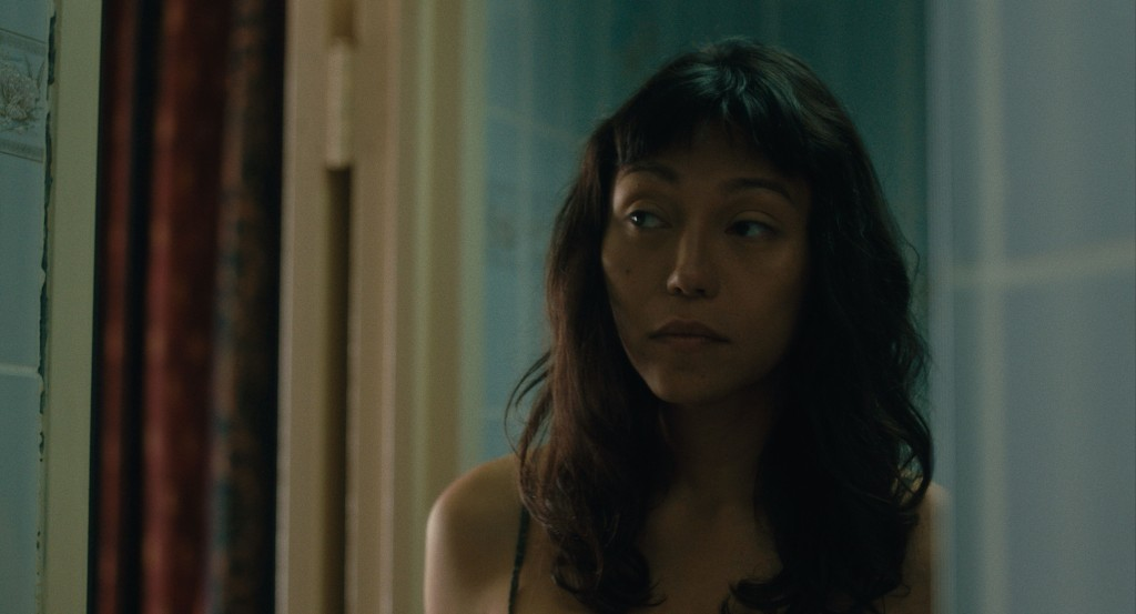 A still from 'Lingua Franca'. Olivia (Isabel Sandoval) is pictured in close-up looking to her right. There are windows behind her but the scene looks set in the evening. She is a Filipino woman with dark skin and a mole on her cheek. Her dark hair is shoulder length with bangs.