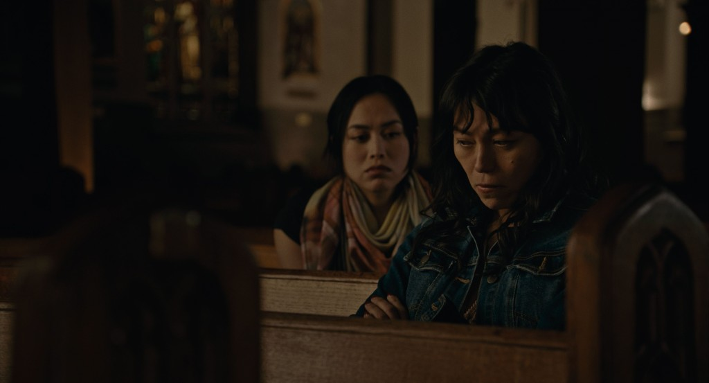 A still from 'Lingua Franca'. Olivia (Isabel Sandoval) sits in a church pew with a friend behind her, she is a another Filipino woman. Olivia looks incredibly fed up, looking downwards with her arms folded, her dark hair looks unwashed and messy, she wears a denim jacket. Her friend in the pew behind has her hair pulled back into a ponytail with a large orange yellow scarf around her neck, she is trying to comfort her.