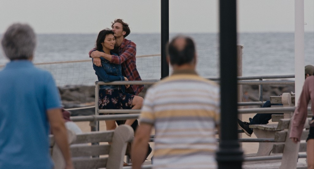 A still from 'Lingua Franca'. Couple Olivia (Isabel Sandoval) and Alex (Eamon Farren) are shot from a distance, and zoomed in. They are near the sea and there are other people walking around the frame. It looks cold. Olivia is staring into the distance, wearing a floral dress and denim jacket, Alex has his arms around her, resting his chin on her head. They both look content.