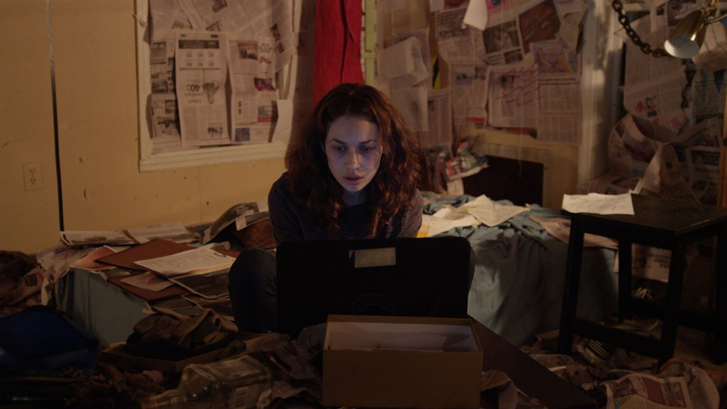 A still from 'Mara'. Kate (Olga Kurylenko)is shown in a mid shot in what is presumably her bedroom. Her pale and gaunt face looks tired, lit by the light of her laptop which she is hunched over. The scene in her room is a mess, the walls are plastered with newspaper and clipping and files scatter the bed and floor.