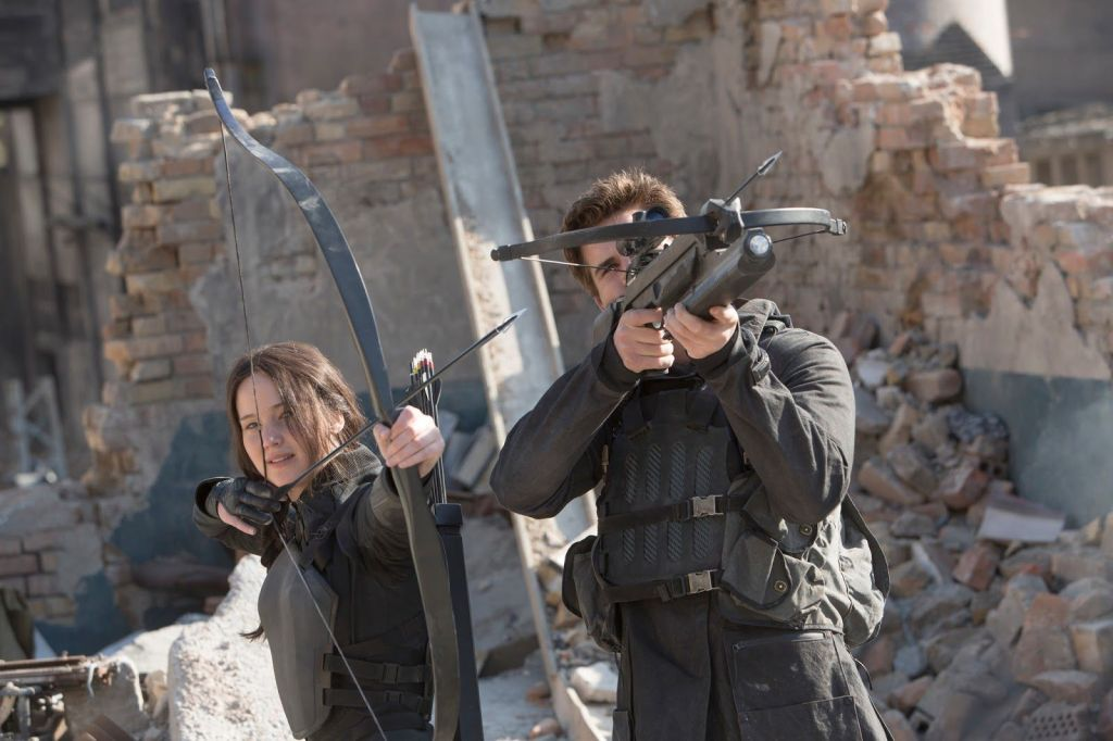 A still from 'The Hunger Games: Mockingjay Part 1'. Katniss Everdeen (Jennifer Lawrence) stands in a demolished war zone with Gale (Liam Hemsworth). Both are wearing military gear, Katniss is aiming her bow at an off-screen target, Gale is pointing his crowwbow in the same direction.