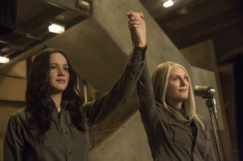 A still from 'The Hunger Games: Mockingjay Part 1'. Katniss Everdeen (Jennifer Lawrence) stands with her arm raised, held in the air by Alma Coin (Julianne Moore). Both women wear grey boilersuits and are shown here in a mid shot. Katniss' shoulder length brown hair is shown here down, different from its usual braid.