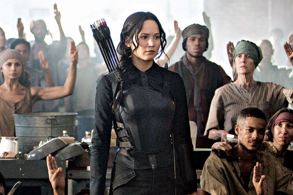 A still from 'The Hunger Games: Mockingjay Part 1'. Katniss Everdeen (Jennifer Lawrence) stands in a room in a crowd of people, they are all impoverished looking, in contrast to Katniss' military style garb and arrows strapped on her back. They are all giving her the Mockingjay salute in solidarity with her as the face of the rebellion.