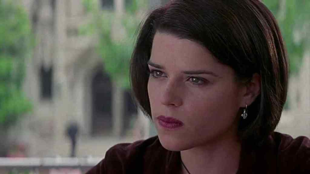 A still from 'Scream 2'. Sidney Prescott (Neve Campbell) is shown her in close-up looking frustrated. She is young and white,wearing a full face of makeup, her dark short hair is tucked behind one ear to reveal a silver earring.