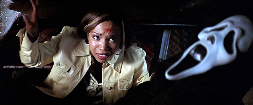 A still from 'Scream 2'. Hallie (Elise Neal) is shown here trying to climb out of a police car window, over the top of an unconscious Ghostface who is sitting in the driver's seat. Hallie is a light skin Black woman with short hair with blonde streaks running through the brunette. She is wearing a light yellow denim jacket and has a visible blood splatter on her forehead.