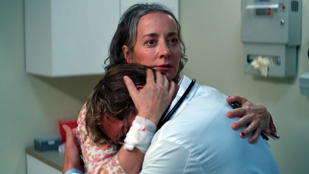 A still from 'She Dies Tomorrow'. Jane (Jane Adams) is  shown in close-up in a Doctors office, yet she is cradling the Doctor as if he has received some terrible news. Jane is staring forward with her piercing dark eyes and her greying hair is stuck to her forehead in a panicky sweat. She grips the back of the Doctor's head as she too looks scared.