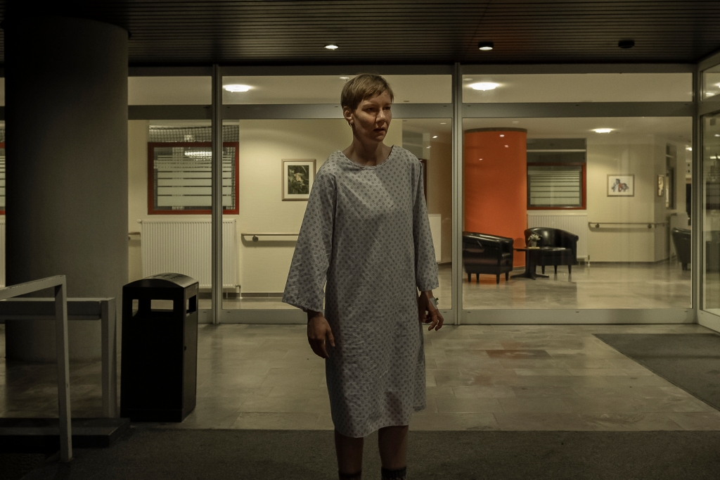 A still from 'Sleep'. Marlene (Sandra Hüller) stands outside a hospital shown in a wide shot. She is wearin a hospital gown, her hair cropped and cheekbones prominent in the nights shadows, she looks disorientated.
