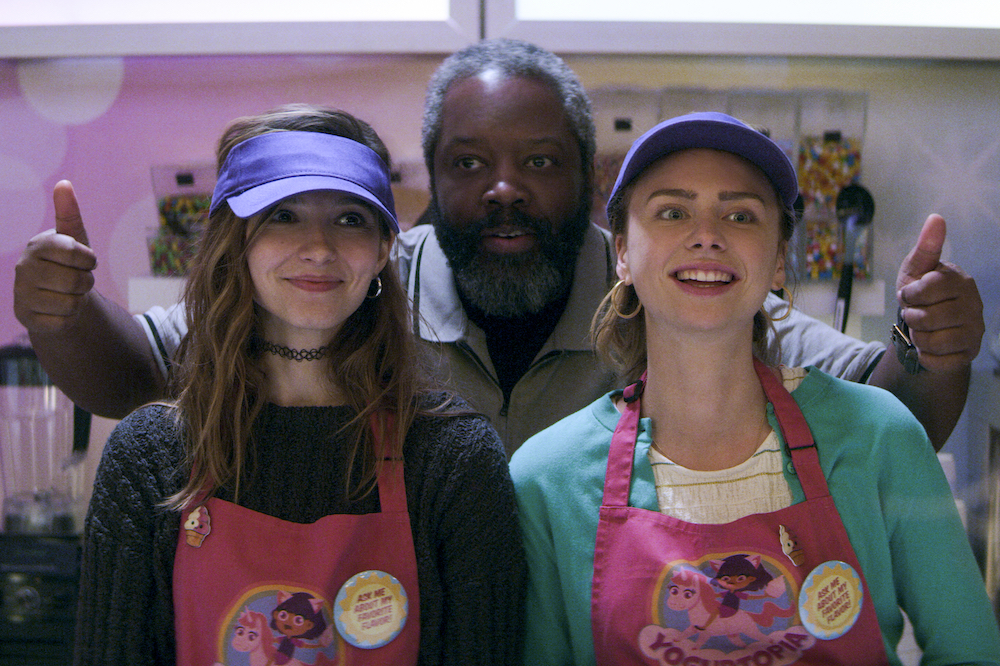 Anjelica Bette Fellini, Kadeem Hardison, and Maddie Phillips in an ice-cream shop. Hardison stands between the two girls as they wear a pink apron and purple caps. He raises two thumbs up over their shoulders.