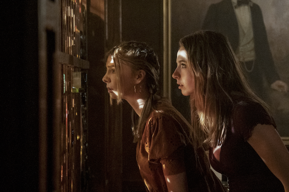 A still from 'Teenage Bounty Hunters'. Maddie Phillips (Sterling) and Anjelica Bette Fellini (Blair) spying through a wine shelf in a wood paneled room. A painting of man hangs on the wall.