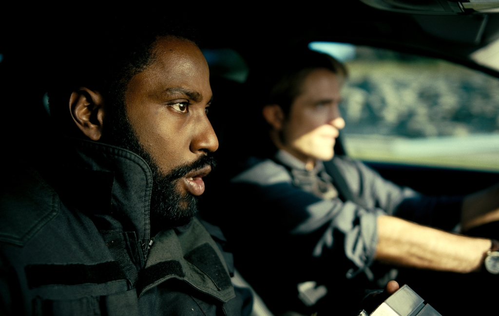 A still from 'Tenet'. The Protagonist (John David Washington) is in a car in the passenger side, shown in close-up. Blurred just next to him in the driver's seat is Neil (Robert Pattinson). Both men are wearing dark colours and bulletproof vests. Neils face seems in control whereas The Protagonist looks in shock.
