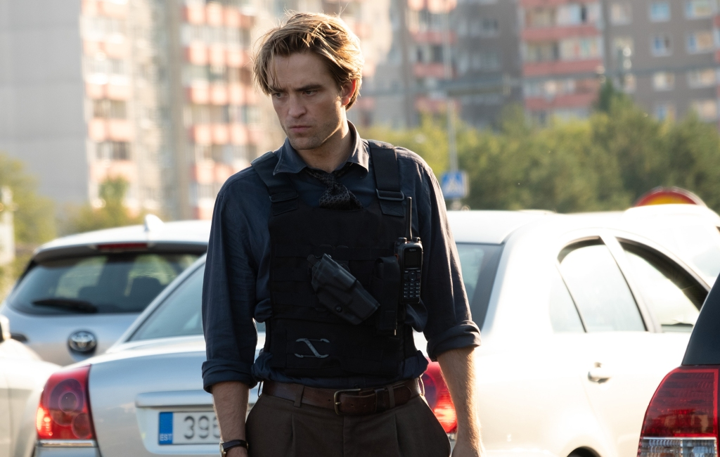 A still from 'Tenet'. Neil (Robert Pattinson) is shown in mid shot in front of some parked cars with a out of focus cityscape behind. He is looking with concentration towards the ground. He is wearing a navy shirt and tie with the bulletproof vest on top, holding a gun and walkie-talkie.